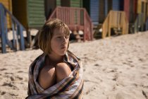 Thoughtful teenage girl wrapped in blanket sitting on beach — Stock Photo