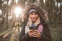 Young woman using mobile phone in forest. — Stock Photo