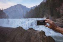 Gros plan de l'homme prend photo de cascade avec téléphone portable — Photo de stock