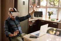 Senior woman mit virtual-Reality-Kopfhörer mit Laptop in der Küche zu Hause — Stockfoto