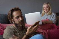 Hombre hablando en el teléfono móvil, mientras que la mujer que usa el ordenador portátil en la sala de estar en casa - foto de stock