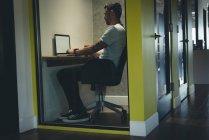 Бизнесмен, используя ноутбук в кабине в офисе — стоковое фото