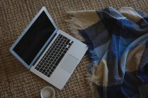 Portátil con taza de café y manta en casa - foto de stock