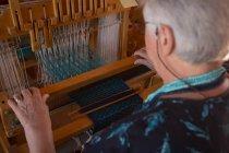 Закри старший жінка, ткацтва з шовку в магазин — стокове фото