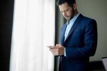 Бизнесмен, пользующийся мобильным телефоном в номере отеля — стоковое фото