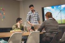 Colegas de trabalho, interagindo uns com os outros na sala na sala de reuniões — Fotografia de Stock