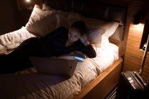 Mujer usando portátil en la cama en el hotel - foto de stock
