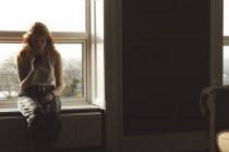 Jovem usando telefone celular em casa — Fotografia de Stock