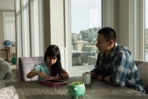 Девушка использует цифровой планшет со своим отцом дома — стоковое фото