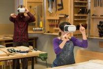 Menuisiers et menuisières utilisant un casque de réalité virtuelle à l'atelier — Photo de stock