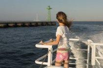 Вдумчивый женщина, стоя на круизном судне — стоковое фото