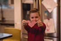 Menino segurando coração forma decoração em casa — Fotografia de Stock
