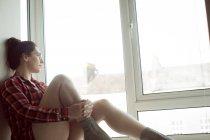 Femme réfléchie dans des lunettes assis sur le rebord de la fenêtre à la maison . — Photo de stock