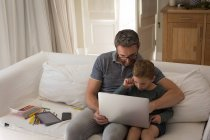 Father and son using laptop in living room at home — Stock Photo
