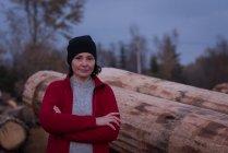 Портрет жінка, стоячи з руки перетнув проти деревини — стокове фото