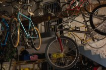 Various bicycle hanging in workshop — Stock Photo