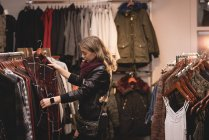 Schöne Mädchen die Auswahl von Kleidung aus dem Regal in Einkaufszentrum — Stockfoto