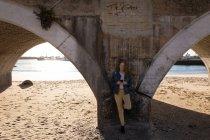 Donna che utilizza il telefono cellulare mentre si appoggia sul ponte alla luce del sole — Foto stock