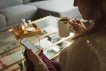Mulher usando celular enquanto tomar café em casa — Fotografia de Stock