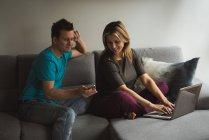 Пара с помощью ноутбука и мобильного телефона в гостиной на дому — стоковое фото