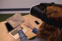 Женщина, касаясь деревянные плиты при использовании гарнитуры виртуальной реальности — стоковое фото