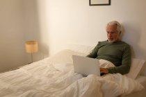 Homme âgé actif utilisant un ordinateur portable dans la chambre à coucher à la maison — Photo de stock