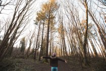 Rear view of woman standing with arms outstretched in forest — Stock Photo