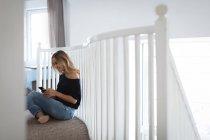 Jeune femme utilisant un téléphone portable à la maison — Photo de stock