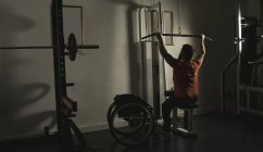 Handicapped man working out at lat pulldown training at gym — Stock Photo