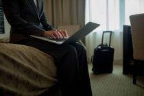 Sección media de la mujer de negocios que utiliza el ordenador portátil en la cama en la habitación de hotel - foto de stock