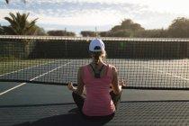 Vista posterior de la mujer realizando ejercicio de yoga en la cancha de tenis - foto de stock