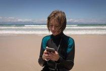 Primo piano di adolescente in muta da bagno utilizzando il telefono cellulare sulla spiaggia — Foto stock