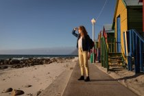 Woman shielding eyes while looking at view near beach huts in sunlight — Stock Photo
