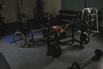 Handicapped man doing chest workout on bench press with barbell in gym — Stock Photo
