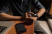 Sección media del hombre usando smartwatch en la mesa - foto de stock