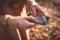 Розділ середині жінка, що використання мобільного телефону під час осінь — стокове фото
