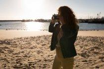 Жінка Беручи фотографії з камери на пляжі на захід сонця — стокове фото