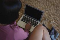 Mujer atenta usando el ordenador portátil en casa - foto de stock