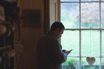 Человек, использующий мобильный телефон возле окна дома — стоковое фото