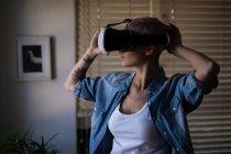 Молода жінка вдома за допомогою віртуальної реальності гарнітура. — стокове фото