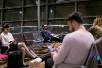 Commuters using electronic devices in waiting room at airport — Stock Photo