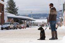 Homme debout avec chien sur le trottoir pendant l'hiver . — Photo de stock
