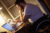 Disabled man looking at documents while using laptop at home — Stock Photo