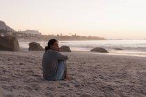 Женщина расслабляющий в песчаный пляж на закате. — стоковое фото