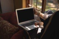 Sección media de la mujer madura usando el ordenador portátil en la sala de estar - foto de stock
