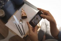 Pregnant woman taking photo of pastry with mobile phone at home — Stock Photo