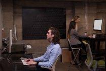 Мужские и женские офисных работников с использованием компьютеров в интерьер офиса — стоковое фото