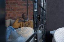 Задумчивый пожилой человек отдыхает дома на диване — стоковое фото