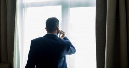Rear view of businessman talking on mobile phone in hotel room — Stock Photo
