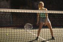 Женщина, практикующая теннис на теннисном корте в солнечный день — стоковое фото